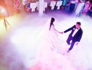 Amazing first wedding dance of newlywed with different colourful light and heavy smoke on restaurant. View from above with guests.